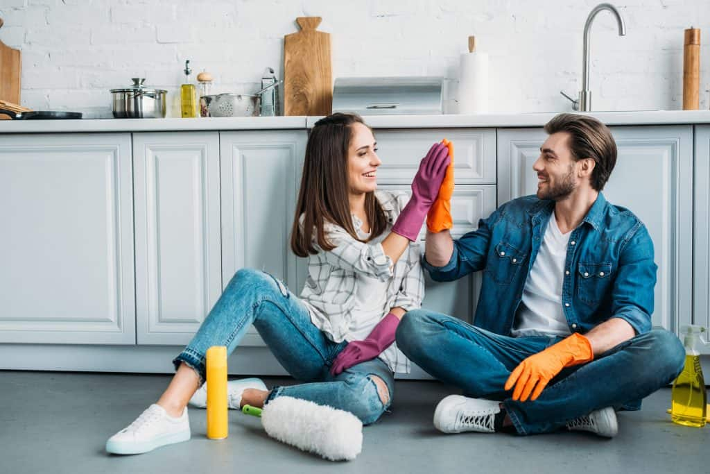 A Couple Finishing Deep Cleaning Their Apartment Kitchen