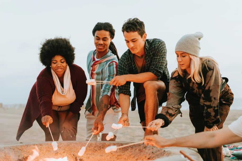 Friends-Roasting-Marshmellows-In-Front-of-Camp-Fire